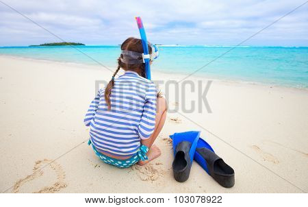 Back view of little girl with snorkeling equipment at beach during summer vacation