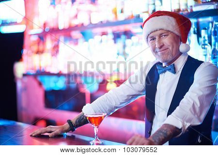 Happy barman in Santa cap standing by counter with martini and looking at camera