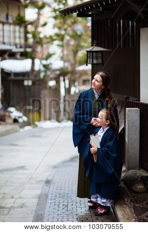 Family of mother and daughter wearing yukata traditional Japanese kimono at street of onsen resort town in Japan going to public hot spring spa.