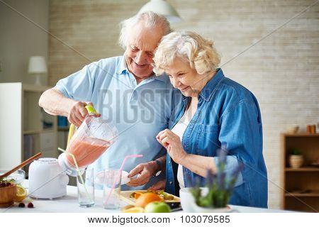 Affectionate senior couple making fruit smoothie in blender