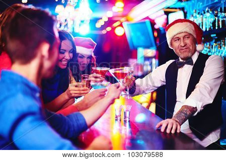 Happy company cheering up by counter with barman in Santa cap near by