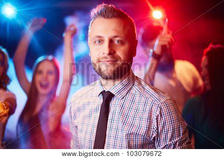 Handsome man looking at camera at party on background of dancing freinds