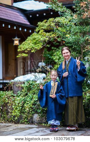 Family of mother and daughter wearing yukata at street of onsen resort town in Japan. Translation of text on wooden plate: passport for round bath visit to protect you from bad luck.