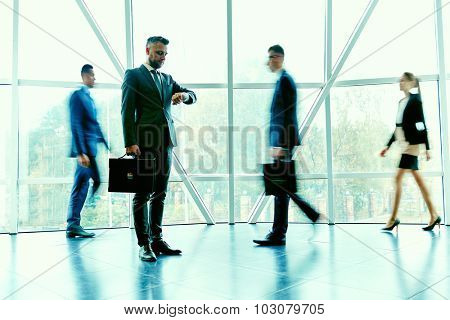 Elegant businessman waiting for partner on background of moving employees inside office building