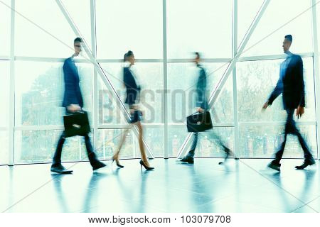 Busy managers moving inside office building