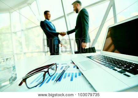 Office stationary items on workplace and handshaking businessmen on background