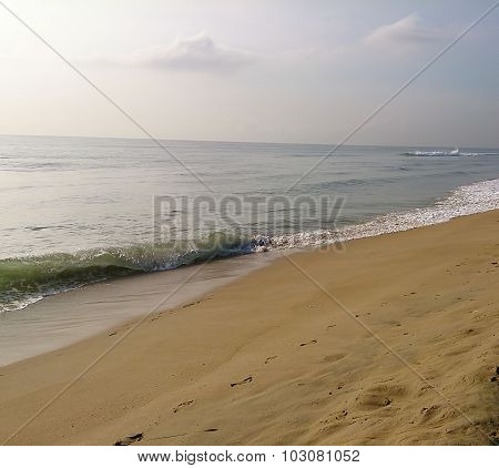 Empty beach sea shore with small waves and yellow sand