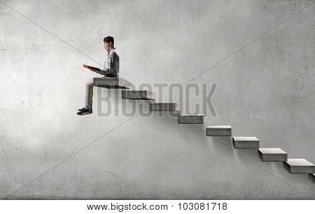 Young man in casual sitting on ladder steps with book in hands
