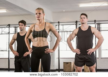 Focused people with hands on hip at the gym