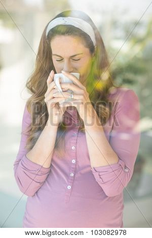 Pregnant woman sipping coffee from cup by window at home