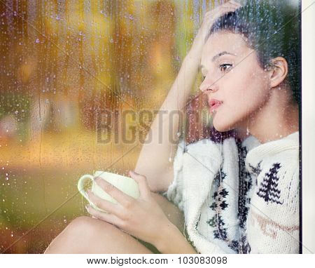 Beautiful thoughtful brunette woman with cup of coffee wearing knitted nordic print poncho sitting home by the window covered with rain drops. Blurred garden fall background reflection.