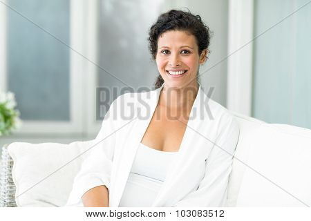 Portrait of happy pregnant woman sitting on sofa at home