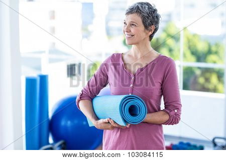 Happy thoughtful mature woman with yoga mat standing at fitness studio