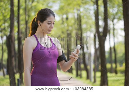 Sporty Asian Woman Listening Music After Jogging In The  Forest
