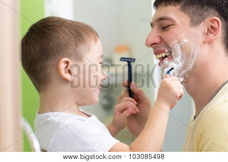 Daddy and his child shaving and having fun in bathroom