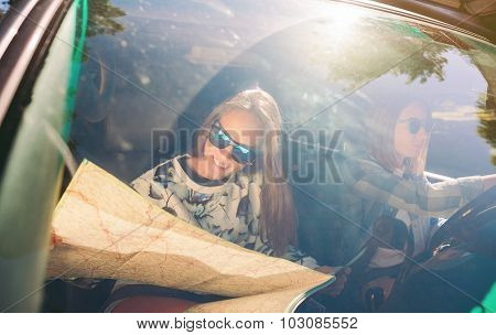 Happy young woman looking a map inside of car