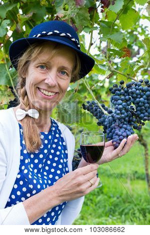 Woman Holding Glass Of Wine Near Bunch Of Blue Grapes