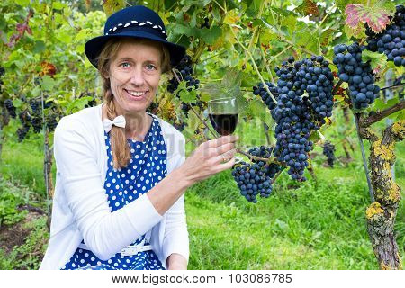 Caucasian Woman Toasting With Glass Of Wine Near Bunches Of Blue Grapes