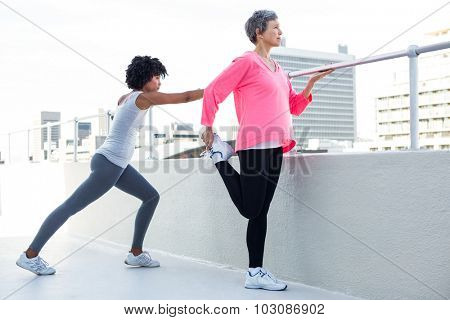 Full length of fit women exercising by railing