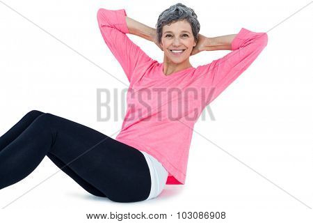 Portrait of mature woman doing sit ups over white background