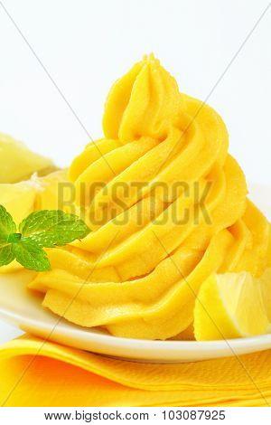 ice cream sundae with swirl of yellow lemon ice cream and fresh lemons