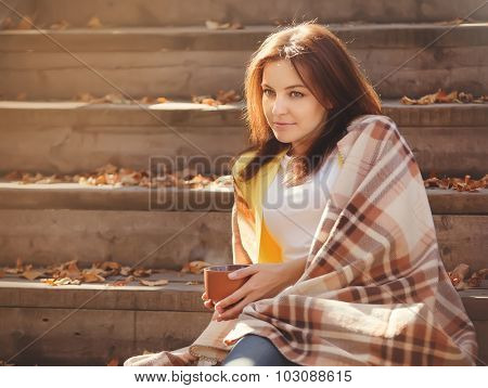 Beautiful girl resting and drinking tea sitting in autumn garden on the steps, wrapped in a woolen plaid blanket.