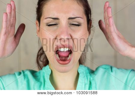 Close-up of screaming woman gesturing with eyes closed while standing by wall at home