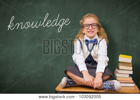 The word knowledge and cute pupil sitting on table against green chalkboard