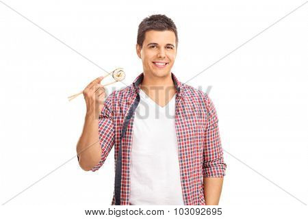 Young man holding a piece of sushi on Chinese sticks and looking at the camera isolated on white background