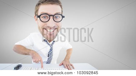 Geeky businessman typing against grey vignette