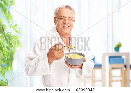 Senior gentleman in a white bathrobe eating cereal at home from a gray bowl and looking at the camera
