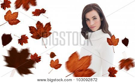 Pretty brunette in white jumper posing against autumn leaves