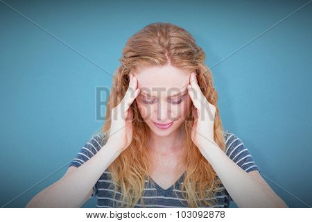 A blonde woman having headache against blue background