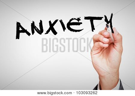 The word anxiety against hand holding a marker