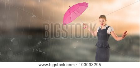 Pretty redhead businesswoman holding umbrella against stormy sea with lighthouse