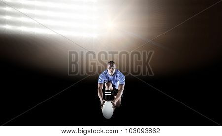 Portrait of rugby player kneeling and holding ball against spotlights