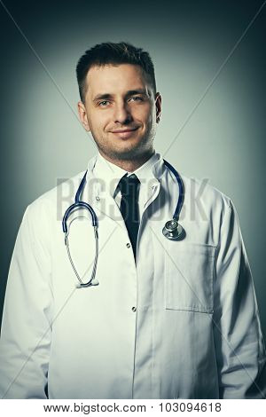 Medical doctor with stethoscope portrait against grey background