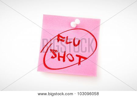 flu shots against pink adhesive note with pushpin