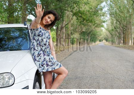 girl on road greeting gesture near white car