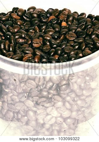 coffee beans in a plastic transparent bucket on white background