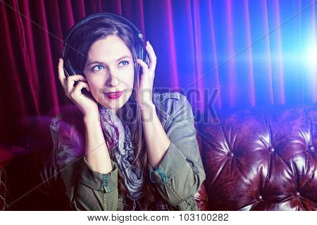 Woman listening to headphones in a club