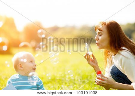 Mother and son making soap bubbles outdoors in park