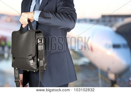 Businessman  Holding Leather Briefcase Checking Time On His Watch At The Airport