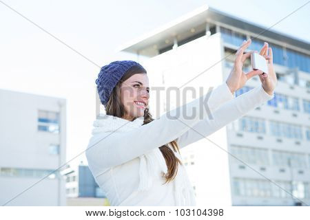 Brunette with warm clothes taking selfie outside