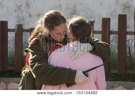 ASHKELON, ISRAEL - JANUARY 10, 2009: israeli soldier from the rescue team hugs young girl who was witness of missile launched by Hamas terrorists from Gaza explode near her house in Ashkelon.