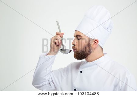 Portrait of a male chef cook holding a soup ladle and smelling it isolated on a white background
