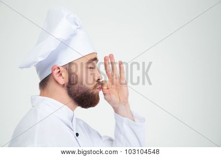 Portrait of a male chef cook smelling something in fingers isolated on a white background