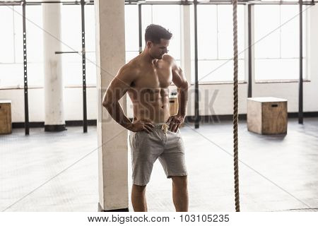Serious muscular shirtless man posing in crossfit gym