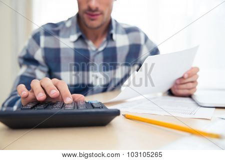 Closeup portrait of a man with calculator checking bills at home