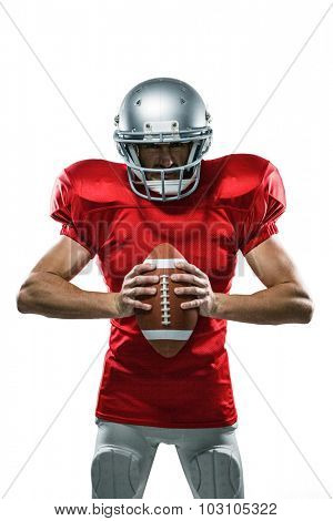 Portrait of furious American football player in red jersey and helmet holding ball on white background